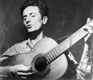 Woody-Guthrie-playing-guitar-520
